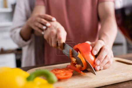 Cropped view of man cutting paprika near girlfriend on blurred background