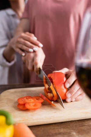 Cropped view of man cutting paprika near girlfriend and glass of wine on blurred foreground