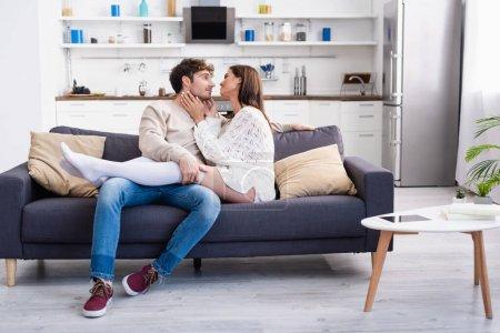 Junge Frau berührt Freund auf Sofa neben digitalem Tablet und Büchern auf Couchtisch