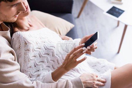 Smartphone avec écran blanc dans les mains de la femme près du petit ami sur le premier plan flou