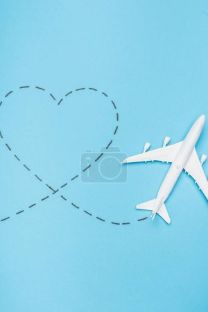 Photo for Top view of white plane model and heart on blue background - Royalty Free Image
