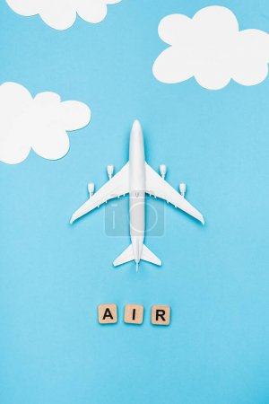 Photo for Top view of plane model and cubes with word air on blue sky background - Royalty Free Image