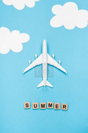 top view of plane model and cubes with word summer on blue sky background