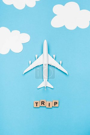 Photo for Top view of plane model and cubes with word trip on blue sky background - Royalty Free Image