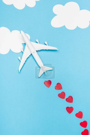 Photo for Top view of plane model and red hearts on blue background with white clouds - Royalty Free Image