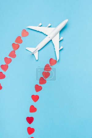 top view of plane model and red hearts on blue background