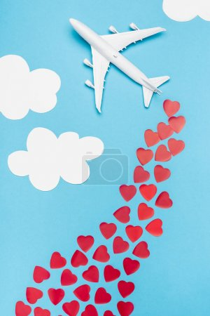 top view of plane model and red hearts on blue background with white clouds