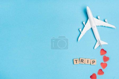 Photo pour Vue du dessus du modèle d'avion, voyage de mot et coeurs rouges sur fond bleu - image libre de droit