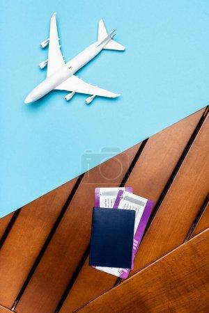 Photo pour Vue du dessus du modèle d'avion blanc et des billets sur fond bleu et bois - image libre de droit