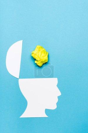 Photo pour Vue du dessus du papier tête humaine et papier froissé sur fond bleu - image libre de droit