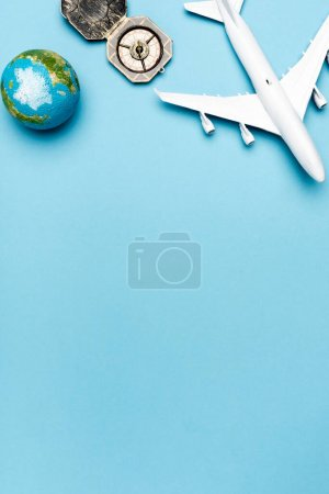 Photo for Top view of white plane model, compass, globe on blue background - Royalty Free Image