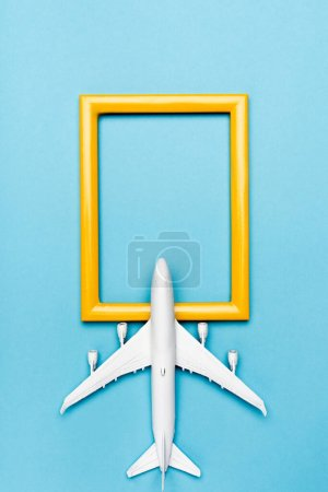 top view of white plane model and empty frame on blue background