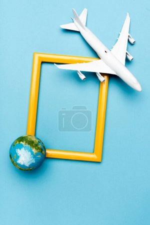 top view of white plane model, globe and empty frame on blue background