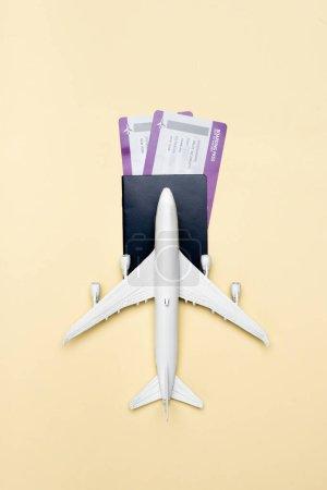 Draufsicht auf weißes Flugzeugmodell und Tickets auf gelbem Hintergrund