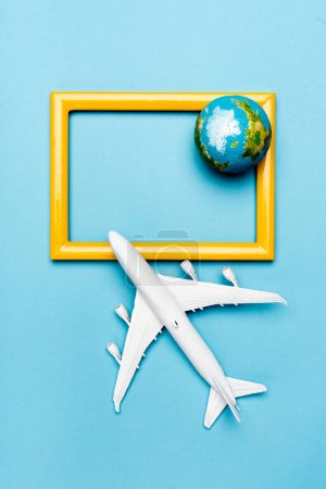 Photo for Top view of white plane model, globe and empty frame on blue background - Royalty Free Image