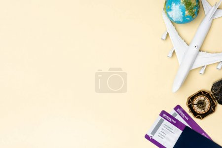 top view of white plane model, compass, globe and tickets on beige background