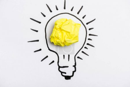 top view of light bulb with crumpled paper on white background
