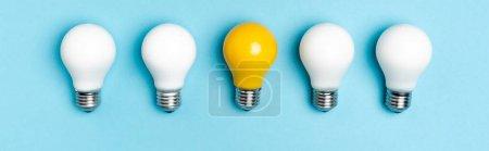 vista superior de bombillas blancas y amarillas sobre fondo azul, pancarta