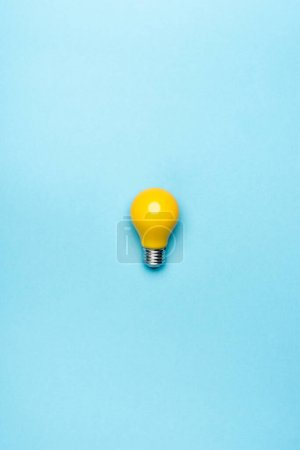 top view yellow light bulb on blue background