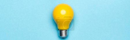 top view yellow light bulb on blue background, banner