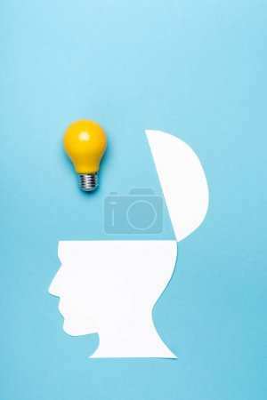 Photo for Top view yellow light bulb and paper human head on blue background - Royalty Free Image