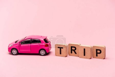 car and word trip on cubes on pink background