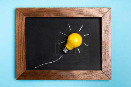 Photo for Top view yellow light bulb and chalkboard on blue background - Royalty Free Image