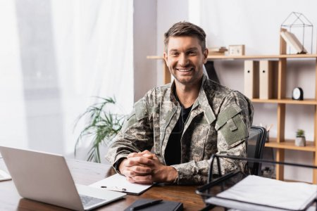 cheerful military man in uniform sitting with clenched hands near laptop on desk