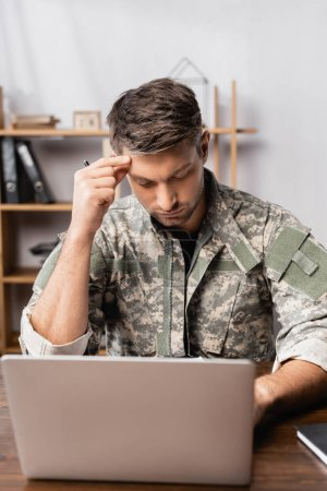 pensive soldier in uniform sitting at desk and using laptop