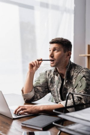pensive soldier in uniform holding pen near laptop with smartphone on blurred foreground