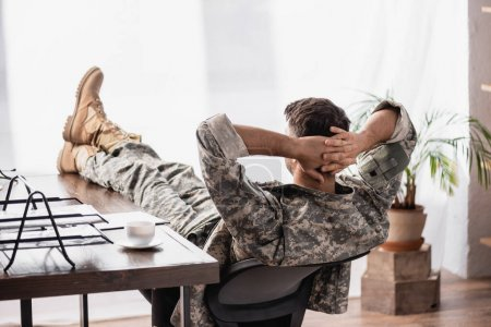 back view of soldier in military uniform resting in office