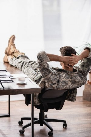 back view of military man in uniform with hands behind back resting in office