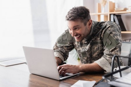 excited military man typing on laptop keyboard