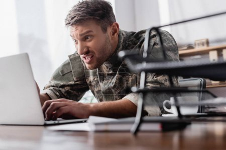 irritated military man typing on laptop keyboard near document tray on blurred foreground