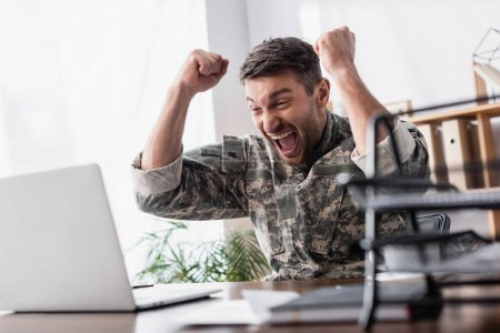 excited military man rejoicing near laptop and document tray on blurred foreground