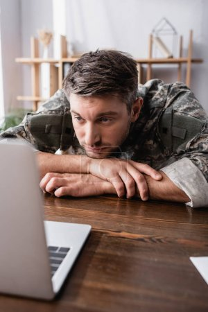 upset military man in uniform looking at laptop on desk
