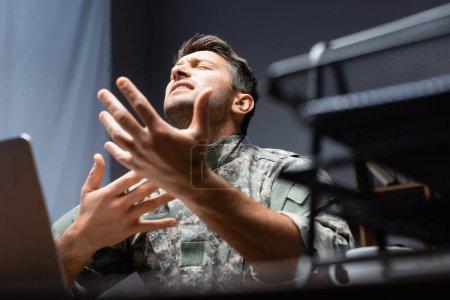 vojenský muž v uniformě gestikulující při vyjadřování pocitů v blízkosti rozmazané zásobníku dokumentů na pozadí