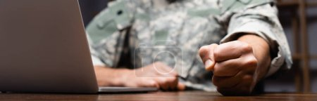 cropped view of military man in uniform sitting with clenched fist near laptop, banner