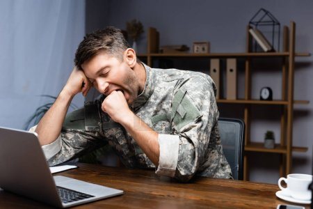 tired military man in uniform sitting with clenched fist while yawning near laptop