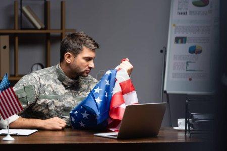 sad military man in uniform holding flag of america near laptop