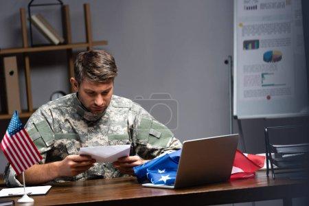 Photo pour Triste militaire en uniforme tenant enveloppe près d'un ordinateur portable et drapeaux américains - image libre de droit