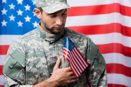 Photo pour Homme militaire patriotique en uniforme et casquette près de l'emblème américain sur fond flou - image libre de droit
