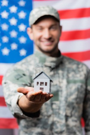 Photo for House model in hand of happy military man in uniform near american flag on blurred background - Royalty Free Image