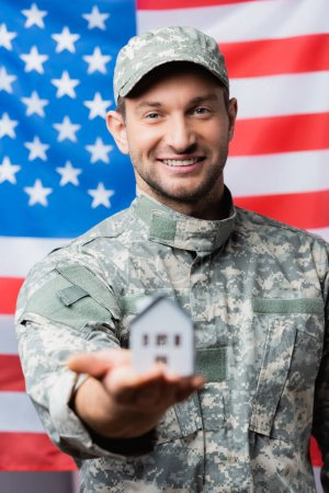 Photo for Happy military man in uniform holding house model near american flag on blurred background - Royalty Free Image