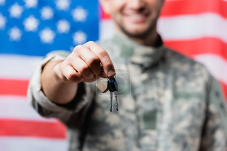 cropped view of happy and patriotic military man in uniform holding keys near american flag on blurred background