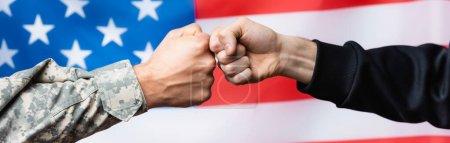 Photo pour Vue recadrée du poing du soldat heurtant un homme civil près du drapeau américain sur fond flou, bannière - image libre de droit