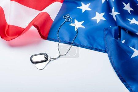 Photo pour Insigne en argent blanc sur chaîne près du drapeau américain sur blanc - image libre de droit