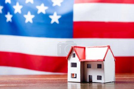 Hausmodell auf hölzernem Schreibtisch neben amerikanischer Flagge auf verschwommenem Hintergrund