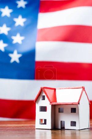 Photo pour Maison modèle près de drapeau américain sur fond flou - image libre de droit