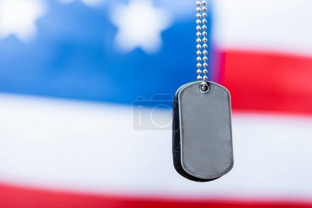 close up of blank metallic badge on chain near american flag on blurred background